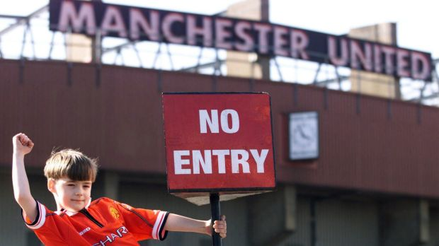 "A young Manchester United fan hung from a ""no entry"" sign at the football club's home stadion after the British ..."