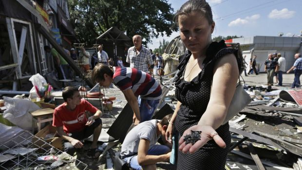 Under siege ... A local woman collects fragments of a shell, after night shelling on a local market, in Donetsk, eastern ...
