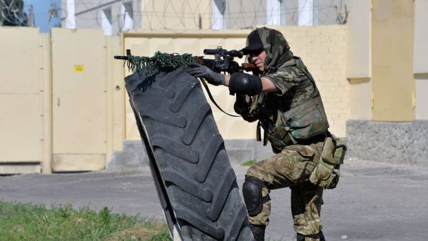 A member of the pro-Ukraine Donbass Battalion stands in firing position during a patrol in the outskirts of the eastern ...