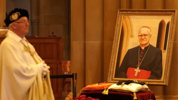 A priest stands close to a portrait of Cardinal Edward Clancy.