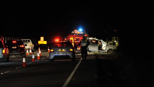 Police attend a fatal car crash on the Federal Highway on Sunday.