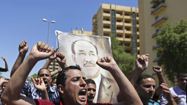 Iraqis chant pro-government slogans bearing a picture of embattled Prime Minister Nouri al-Maliki in Baghdad on Monday.