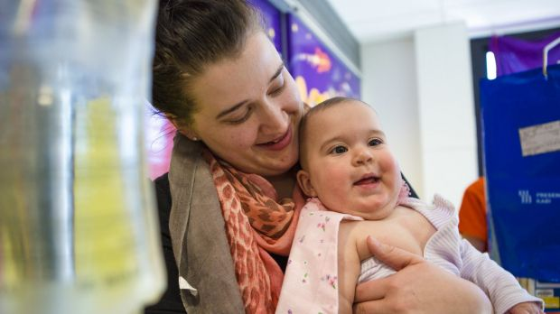 Tjanara Nageeb, and her daughter Eva, 10 months, at the launch of Capes 4 Kids at the Canberra Children's Hospital.