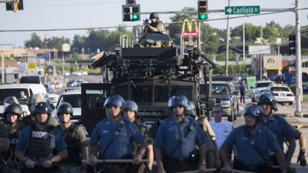 Clash: Riot police stand guard as demonstrators protest in Ferguson in August.