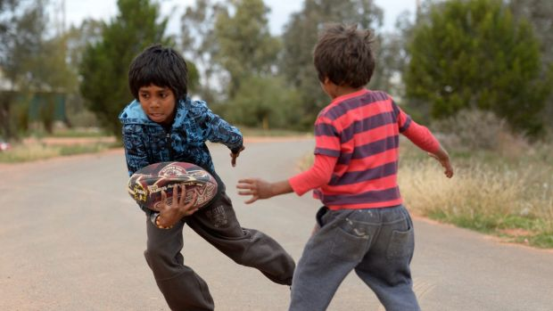 Aboriginal kids in Namatjira Avenue in Dareton near Mildura playing footy on the street.