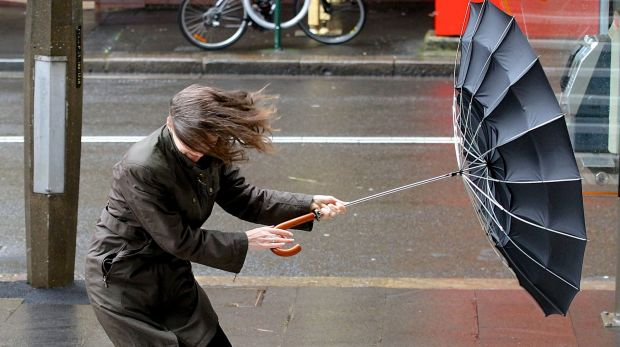 Commuters battle the conditions in the Sydney CBD.
