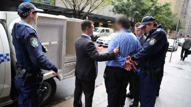 Police lead the 34-year-old man from a Martin Place office.