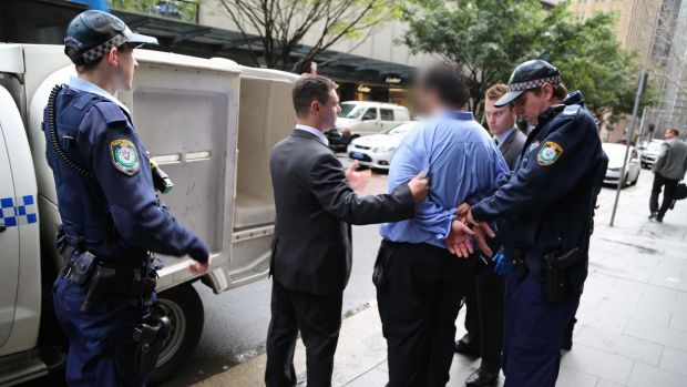 Police lead the 34-year-old lawyer from his Martin Place office.