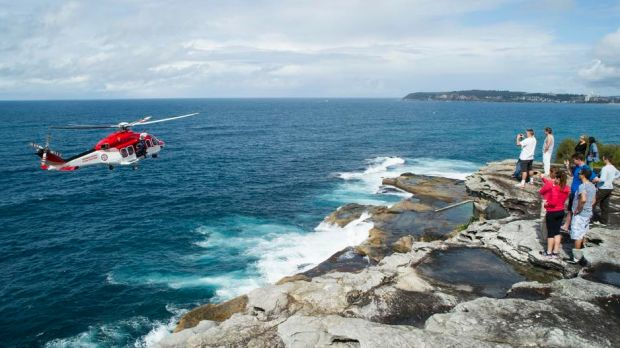 A rescue helicopter attends the scene where a rock fisherman died on the northern beaches.