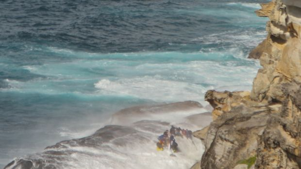 A wave sweeps over rescuers on the rock shelf at North Curl Curl.