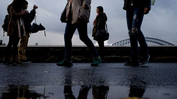 Tourists dodge puddles for photos in the Sydney Botanic Garden.