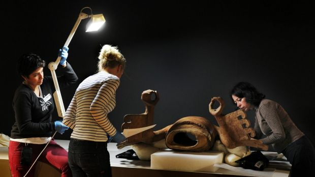 Australian Museum staff work on the Eagle Warrior sculpture on loan from Museo del Templo Mayor in Mexico.