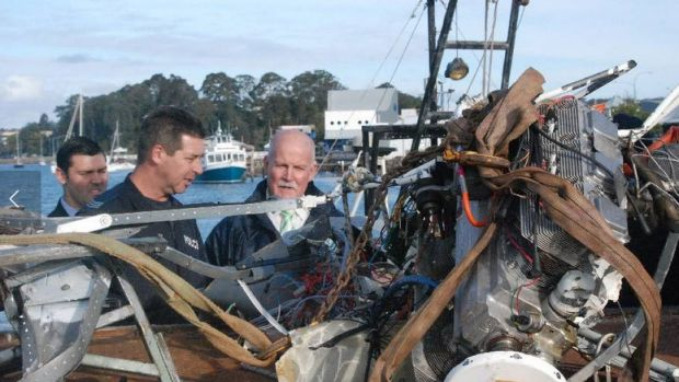 Investigators with some of the wreckage from the July 6 plane crash off Barlings Bay.