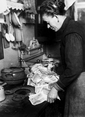 Easy come, easy go: A German woman burns worthless banknotes during the Weimar Republic.