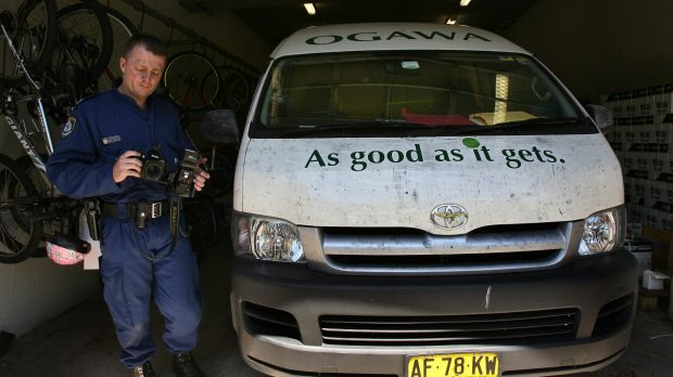 A police officer  finger printing and photographing Mr Chin's van.