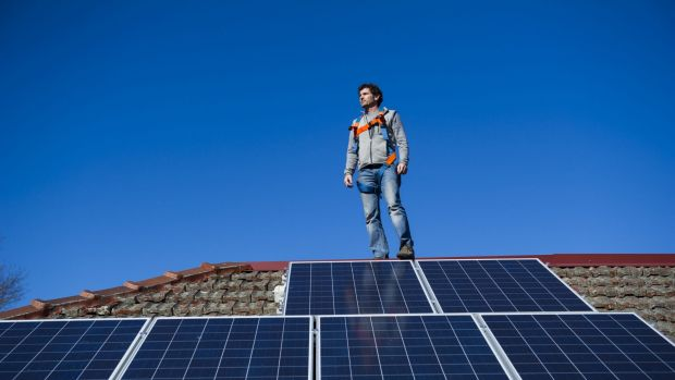 Armada director Justin Ryan with some solar panels his company installed on an Ainslie rooftop. Mr Ryan said he hoped ...