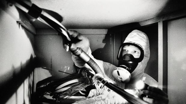 Dmark Giersch wears protective gear while in a cupboard of a house in Campbell to vacuum away dust and asbestos that may ...