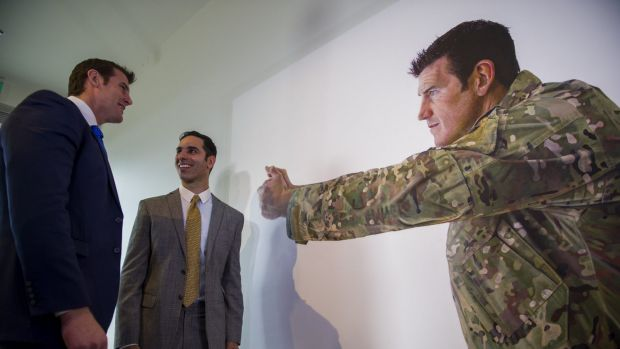 Artist Michael Zavros, right, with one of two portraits of Ben Roberts-Smith VC, MG, left, at the Australian War ...