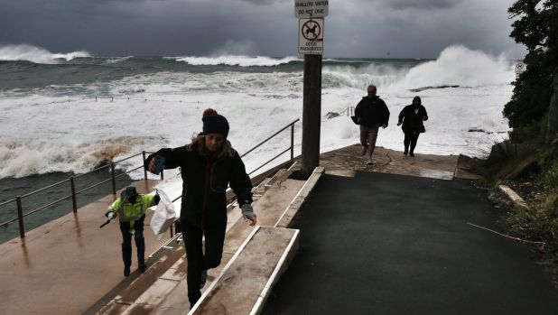 Sightseers scramble to safety as big waves lash Dee Why beach.