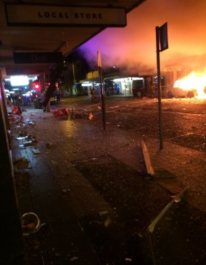 A car caught fire while shards of glass littered the street after the explosion.