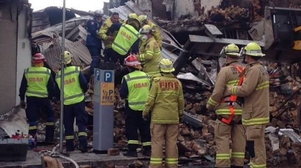Devastation: firefighters search through the rubble.