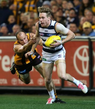 Cameron Guthrie evades David Hale during the AFL 2nd Qualifying Final match between the Hawthorn Hawks and the Geelong ...
