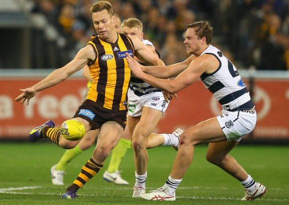 Sam Mitchell of the Hawks kicks whilst Mitch Duncan of the Cats attempts to smouther during the AFL 2nd Qualifying Final ...