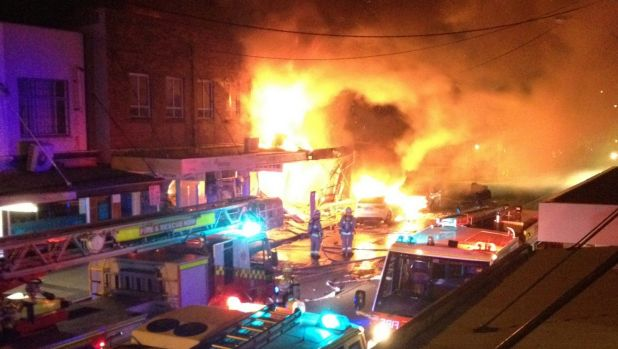 The fire destroys shops and apartments on Darling Street.