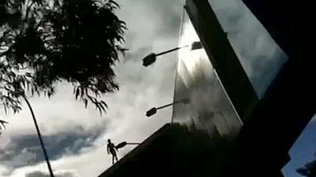 A naked man was filmed standing on the Wellington Street billboard, opposite Perth's train station, by two university ...