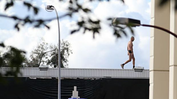 A naked man thought to be carrying a handgun was surrounded by police on Saturday after he climbed atop a Perth city ...