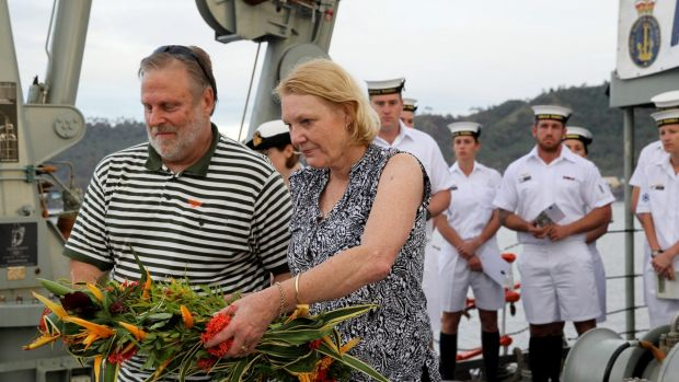 A time to remember: Graham and Robyn Rosentrauss prepare to drop flowers off the stern of HMAS Yarra.