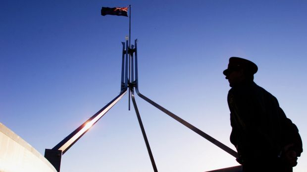 A Parliament House security officer keeps a watchful eye on the roof of Parliament House in Canberra.