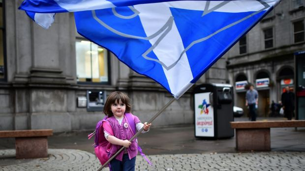 A child plays with a pro-independence 'Yes' flag on the streets of Aberdeen in Scotland, ahead of the referendum on ...
