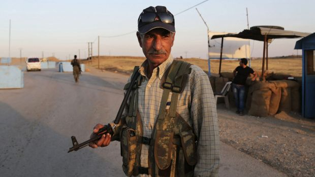 Syrian Kurdish Peshmerga fighters stand guard at a refugee camp in Derike, Syria.