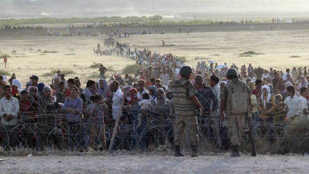 Turkish soldiers stand guard as Syrians wait behind the border fences near the southeastern town of Suruc in Sanliurfa ...