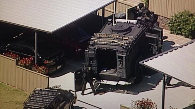 SERT officers at the scene of a siege at Inala. Photo: Jess Millward/Nine News