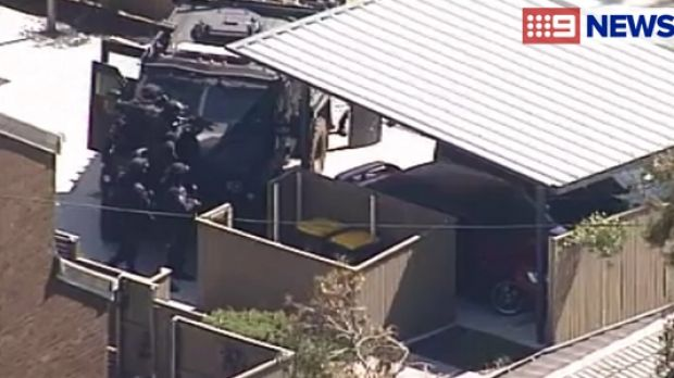Police surround a man during a siege at an Inala home.
