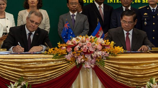 Australia's then immigration minister Scott Morrison and Cambodian Interior Minister Sar Kheng sign an agreement to ...