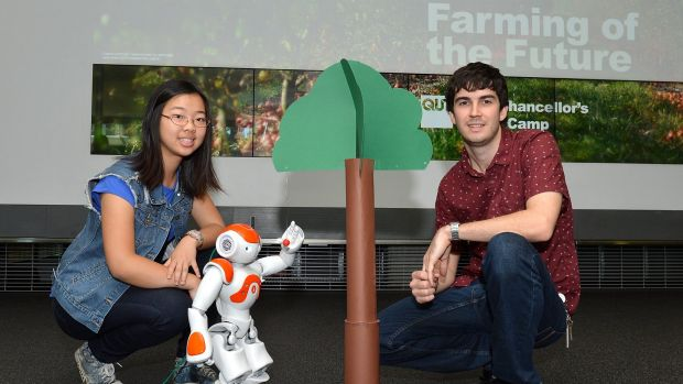 Student Eva Wang and QUT lecturer Christopher Lehnert with a robot designed to pick fruit.