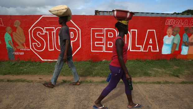 People pass an Ebola awareness mural in Monrovia, Liberia. More than 3,200 people have died in West Africa due to the ...