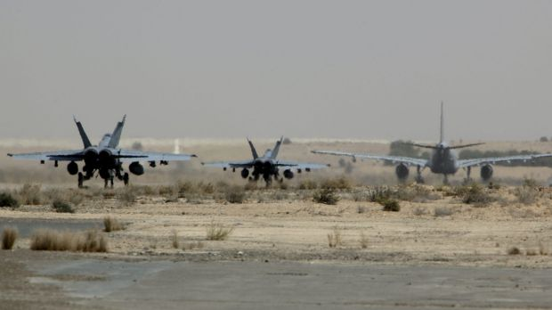 Two RAAF Super Hornets following a Multi-Role tanker transport along a taxiway to commence a mission in Iraq.