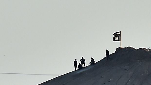 STAKING CLAIM: An Islamic State flag is planted on a small hill outside Kobane.