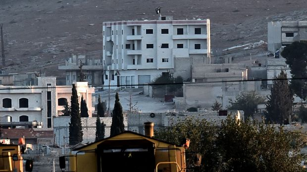 ATTACK SIGNAL: Islamic State militants raise their flag on a building on the eastern edge of Kobane.