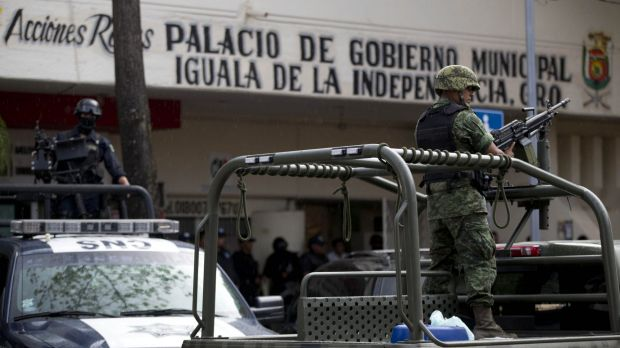 On guard: Armed vehicles in Iguala, near where 28 bodies have been found in a mass grave.