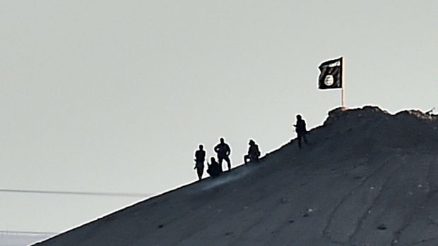 Laying claim: Islamic State militants planted a flag atop a hill in the Syrian town of Kobane.