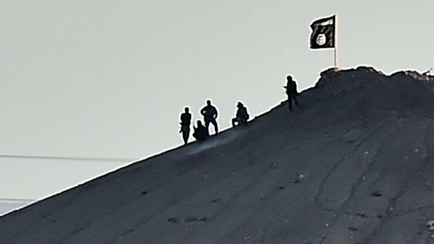Strategic: Islamic State militants stand atop a hill in the Syrian town of Kobane.