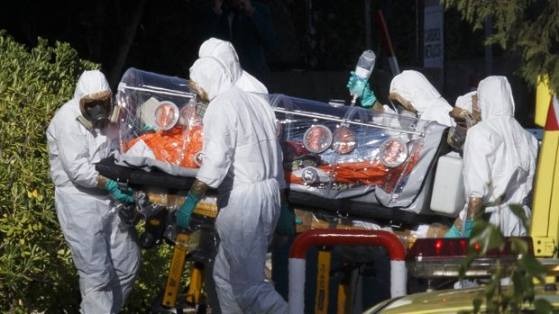 Health workers transfer Ebola patient Father Miguel Pajares to a hospital in Madrid after flying him back from Liberia. ...