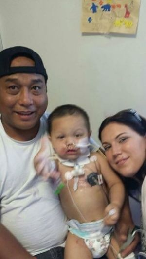 "DISFIGURED: Bounkham ""Bou Bou"" Phonesavanh with his parents after being injured in a police raid."