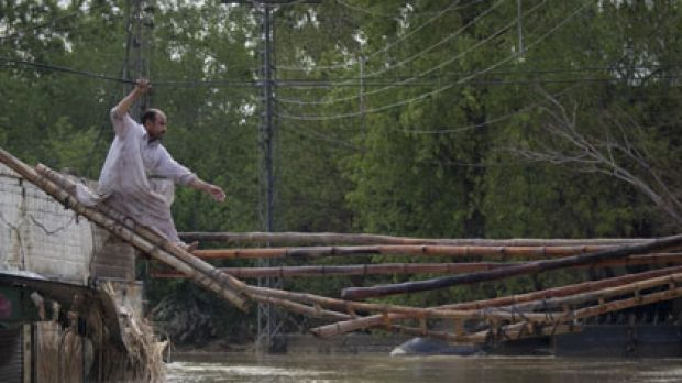 Endless struggle ... a man tries to cross a makeshift bridge to escape his flooded home in Nowshera.