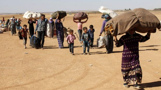 Syrian Kurdish refugees head for the Turkish town of Suruc on Tuesday.